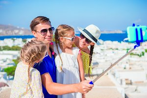Family vacation in Europe. Parents and kids taking selfie background Mykonos island