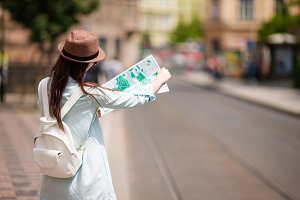 Youn girl with citymap walking on european streets. Travel caucasian woman with map outside during holidays in Europe.