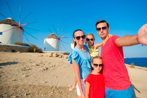 Family of four taking selfie with a stick in front of windmills at popular tourist area on Mykonos island, Greece