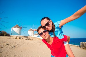 Young couple taking selfie with a stick in front of windmills at popular tourist area on Mykonos island, Greece