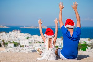 Little girl and happy dad in Santa Hats enjoy Christmas vacation with beautiful view