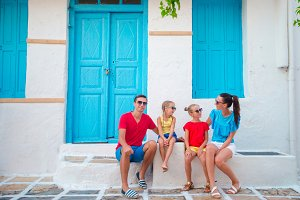 Family in Mykonos on summer vacation. Parents and kids at narrow street in traditional greek village
