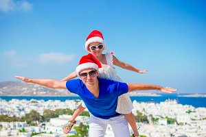 Family in Santa Hats enjoy greek vacation with beautiful view