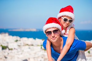 Portrait of family in Santa Hats enjoy Christmas vacation with beautiful view.