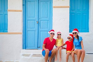 Family in Santa hats on Christmas vacation. Parents and kids at street of typical greek village on Mykonos Island, in Greece