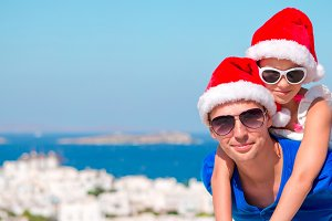 Portrait of little girl and happy dad in Santa Hats enjoy Christmas vacation with beautiful view. Panorama on old Mykonos village in Greece.