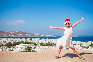 Little funny girl in red Santa hat outdoors background of Mykonos. Kid at street of typical greek traditional village with white walls and colorful doors on Christmas vacation in Greece