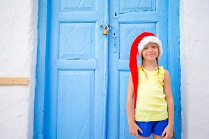 Little girl in santa hat outdoors in old street on Christmas vacation in Mykonos.
