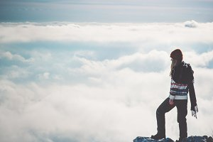 Traveler alone on cliff over clouds