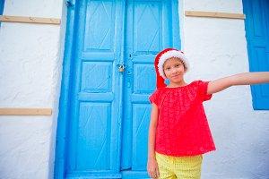 Adorable litttle girl in Santa Hat taking selfie at narrow street backgrounnd blue door