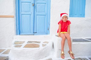 Little girl in santa hat outdoors in old street on Christmas vacation in Mykonos. Kid at street of typical greek traditional village with white walls and colorful doors on Mykonos Island, in Greece