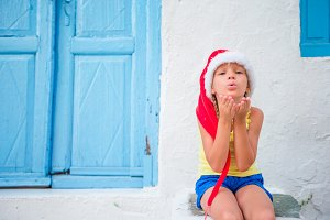 Little girl in santa hat outdoors in old street on Christmas vacation in Mykonos. Kid at street of typical greek traditional village sends kisses