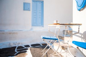 Beautiful cafe on a street of typical greek traditional village on Mykonos Island, Greece. Coffee on table for breakfast