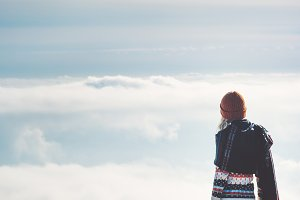 Woman alone on cliff over clouds