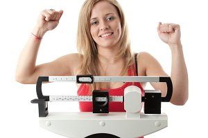 Young woman celebrating on the scale