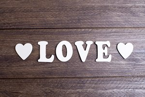 Word love with white letters between two hearts on brown wood.