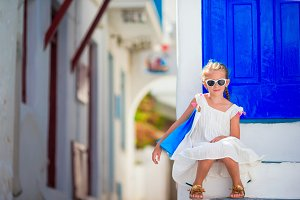 Little cute girl portrait outdoors in old greek village. Kid at street of typical greek traditional village with white walls and colorful doors on Mykonos Island, in Greece