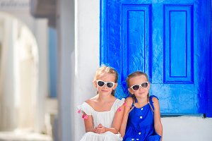 Little happy girls in dresses at street of typical greek traditional village with white walls and colorful doors on Mykonos Island, in Greece