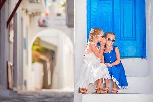 Little girls at street of typical greek traditional village on Mykonos Island, in Greece
