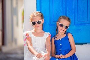 Portrait of Little smiling girls sitting near old blue door in greek Mykonos village, Greek