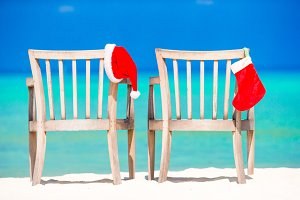Christmas on beach chairs in cafe with Santa hats at sea