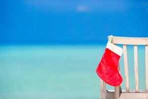 Santa Claus Sock on chair near tropical beach with turquoise sea water and white sand. Christmas vacation concept