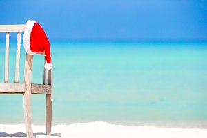Santa Claus Hat on chair near tropical beach with turquoise sea water and white sand. Christmas vacation concept