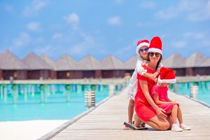 Family in Santa hat on Christmas beach vacation