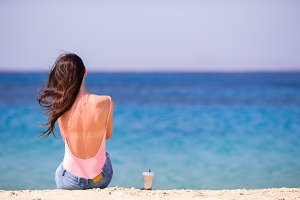 Young woman with coffee on the beach during tropical vacation. Girl enjoy her wekeend on one of the beautiful beaches in Mykonos, Greece, Europe.