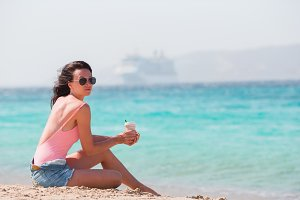 Young beautiful woman with coffee on the beach during tropical vacation.