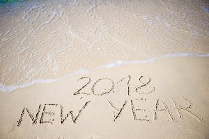 2018 New Year written in the white sand