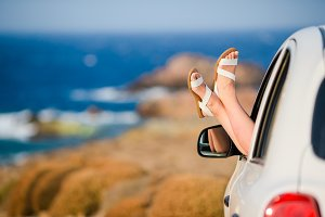 Closeup of female feet showing from car window background sea