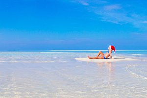 Little girl in Santa hat on white beach during Xmas vacation
