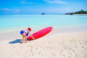 Little girl in Santa hat during beach vacation on tropical vacation