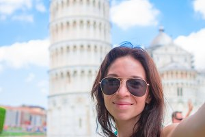 Tourist woman taking selfie background famous Pisa Tower. Woman traveling visiting The Leaning Tower of Pisa.