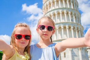 Little adorable girls taking selfie background the Leaning Tower in Pisa, Italy. Photo about european vacation