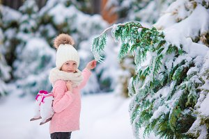 Adorable little girl going to skate in warm winter snow day outdoors