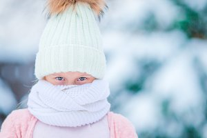 Portrait of little adorable girl in snow sunny winter day, Closeup beautiful green eyes.