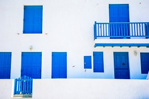 Traditional houses with blue doors and windows in the narrow streets of Mykonos, Greece.