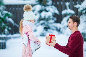 Young father gives Christmas gift to his little adorable daughter