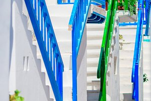 Amazing colorful stairs on beautiful narrow streets of greek island with balconies and white houses. Beautiful architecture building exterior with cycladic style.