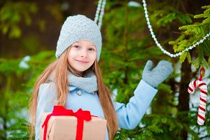 Adorable girl with christmas box gift in winter outdoors on Xmas eve