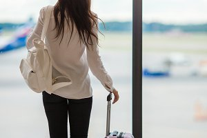 Young woman near big panoramic window in an airport lounge waiting for arrive
