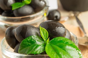 Black olives with green leaves