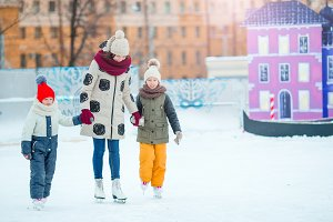 Little adorable girls with mother learning to skate on ice-rink