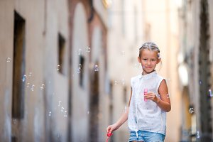 Little girl blowing soap bubbles in european city. Portrait of caucasian kid enjoy summer vacation in Italy