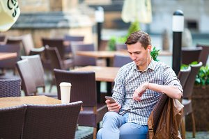 Young man with cellphone outdoors in outdoor cafe. Man using mobile smartphone.