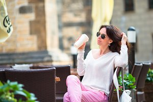 Happy young urban woman drinking coffee in Europe. Caucasian tourist enjoy her european vacation in empty city