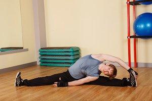 Man sitting on cross splits