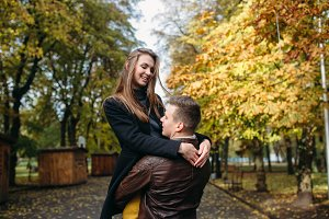 attractive happy couple walking in autumn park